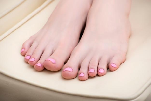 Weibliche füße mit einer rosa pediküre