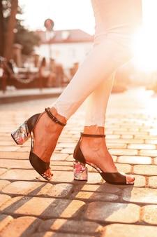 Weibliche füße mit modischen schwarzen schuhen in der stadt bei sonnenuntergang, nahaufnahme