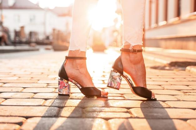 Weibliche füße mit modischen schwarzen schuhen in der stadt bei sonnenuntergang