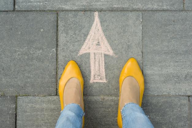Weibliche füße mit pfeil gemalt auf dem grauen bürgersteig