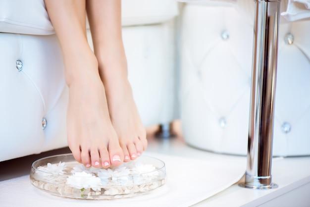 Weibliche füße mit spa-schüssel, handtuch und blumen auf weiß