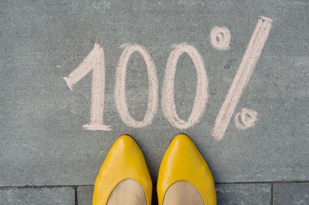 Weibliche füße mit text 100 prozent auf grauem bürgersteig geschrieben.