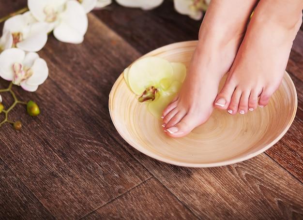 Weibliche füße mit wassertropfen, badekurortschüsseln, tücher