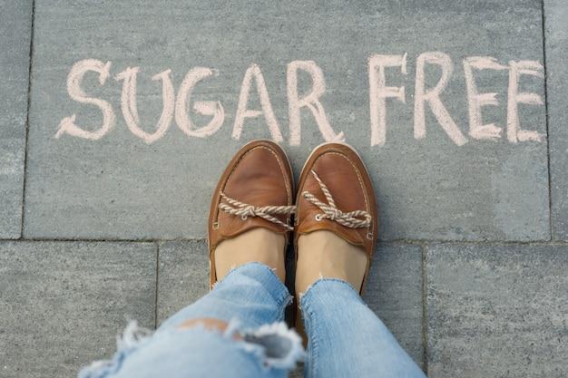 Weibliche füße mit zuckerfreiem text geschrieben auf grauem bürgersteig