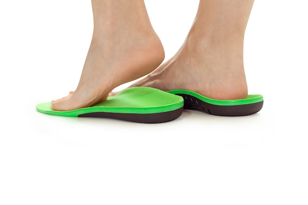 Weibliche füße stehen in orthopädischen einlegesohlen
