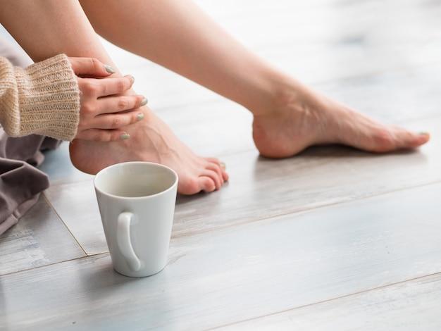 Weibliche füße und eine tasse tee oder kaffee. kaffeezeit und erwachenskonzept