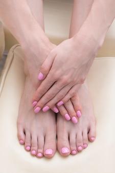 Weibliche füße und hände mit einer rosa maniküre. schönheitssalon. nahansicht