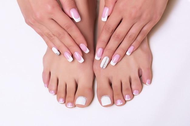 Weibliche füße und hände mit luxuriösen maniküre- und pedikürenägeln