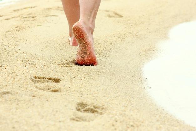 Weibliche fußabdrücke im sand am strand