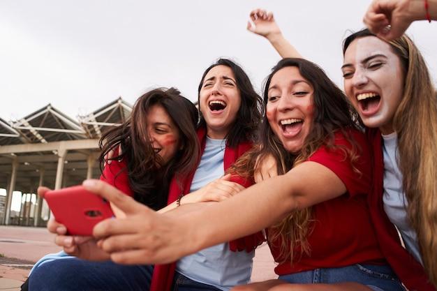 Weibliche fußballfans, die während des fußballspiels auf das telefon schauen