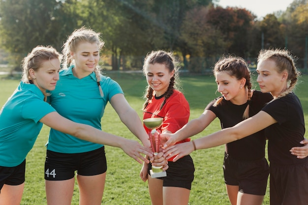 Weibliche fußballmannschaft, die eine trophäe hält