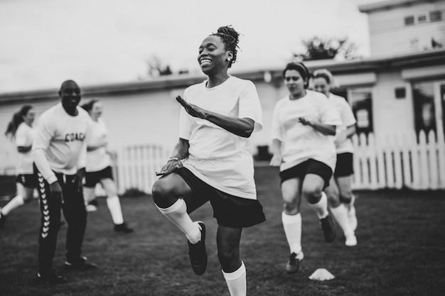 Weibliche fußballspieler, die auf dem feld aufwärmen