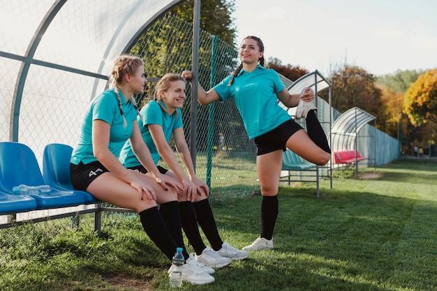 Weibliche fußballspieler, die auf einer bank sitzen