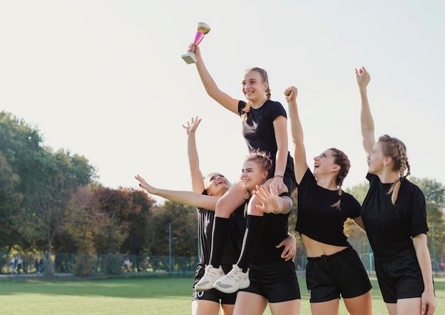 Weibliche fußballspieler, die eine trophäe gewinnen