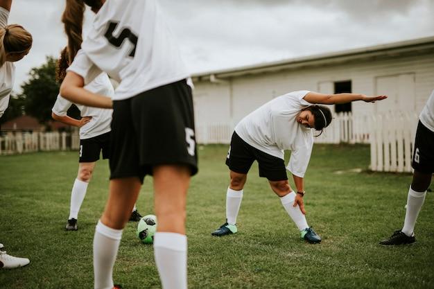 Weibliche fußballteamspieler, die vor spiel ausdehnen