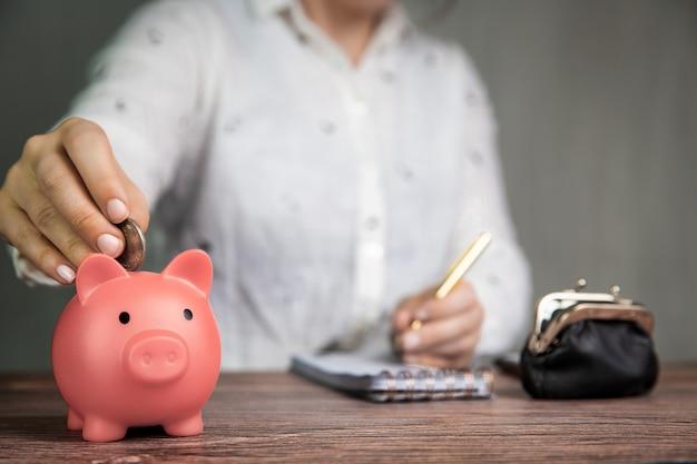 Weibliche geschäftsfrau, die verwaltung tut, zählt und geld mit rosa sparschwein spart
