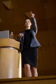 Weibliche geschäftsführerin, die zeigt, während sie eine rede im konferenzzentrum hält