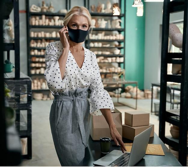 Weibliche geschäftsinhaberin in schützender gesichtsmaske, die im stehen telefoniert und laptop benutzt