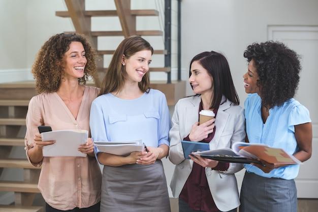 Weibliche geschäftskollegen, die zusammen mit datei und digitaler tablette stehen