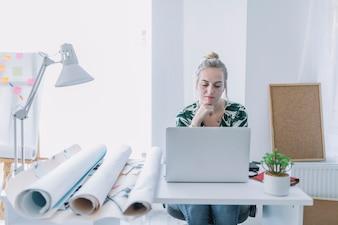 Weibliche Geschäftsfrau, die an Laptop am Arbeitsplatz arbeitet