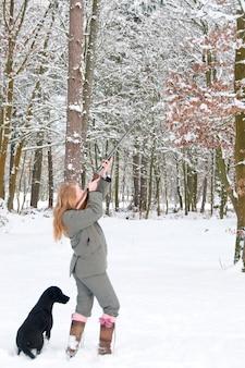 Weibliche gewehr mit labrador heraus auf einem schneebedeckten trieb