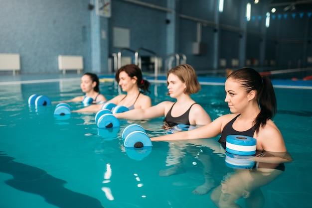 Weibliche gruppe, die übung mit hanteln auf aqua-aerobic-training im schwimmbad tut. frauen in badebekleidung auf training, wassersport