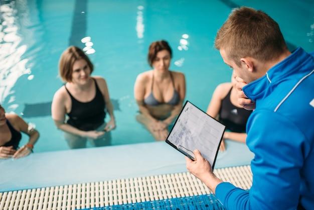 Weibliche gruppe mit männlichem trainer, aqua-aerobic im schwimmbad. frauen in badebekleidung auf training, wassersport