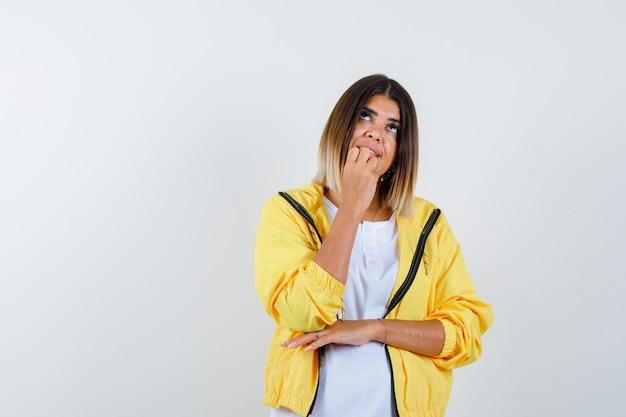 Weibliche händchenhaltende hand am kinn im t-shirt, in der jacke und im träumerischen aussehen, vorderansicht.