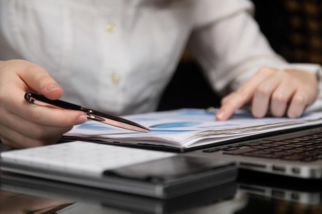 Weibliche hände arbeiten mit diagramm a des notizbuches