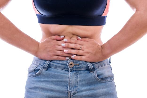 Weibliche hände auf dem bauch. schmerzen im magen- oder zyklusschmerzkonzept isoliert
