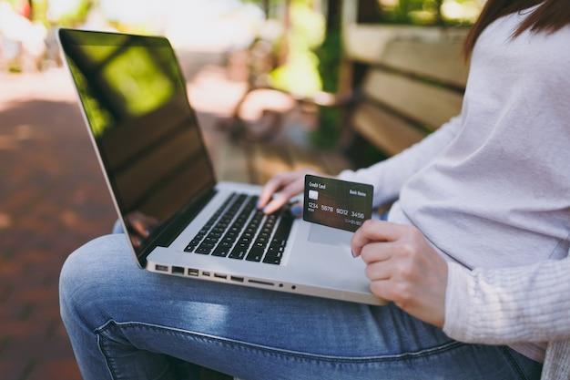 Weibliche hände auf der tastatur hautnah. frau, die auf der bank mit kreditkarte sitzt und draußen an einem modernen laptop-pc mit leerem leerem bildschirm arbeitet. mobiles büro. online-shopping, geschäftskonzept.