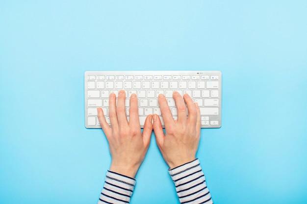 Weibliche hände auf einer tastatur auf einer blauen oberfläche. konzept der büroarbeit, freiberuflich, online. . flachgelegt, draufsicht