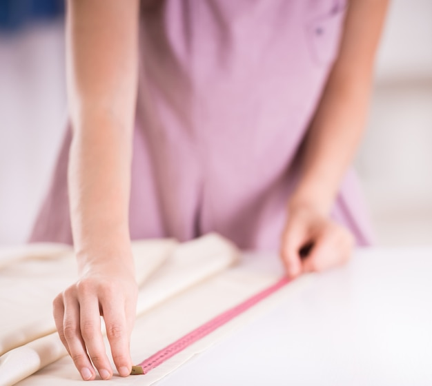 Weibliche hände bei der arbeit mit messendem band, nahaufnahme.
