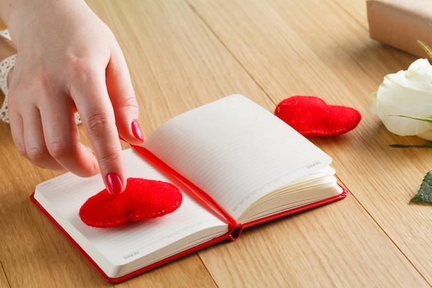 Weibliche hände berühren rotes herz auf tagebuch für valentinstag mit geschenkbox