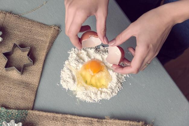 Weibliche hände brechen ein hühnerei in mehl