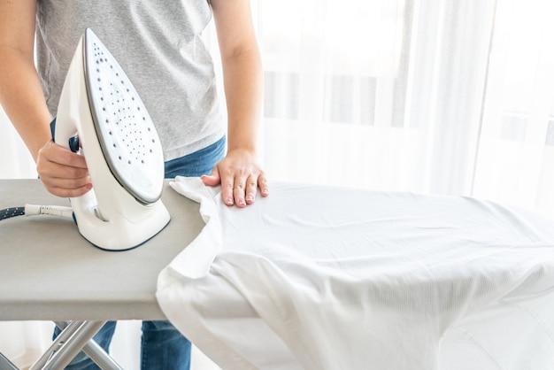 Weibliche hände dämpfen bügelndes weißes hemd auf bügelbrett