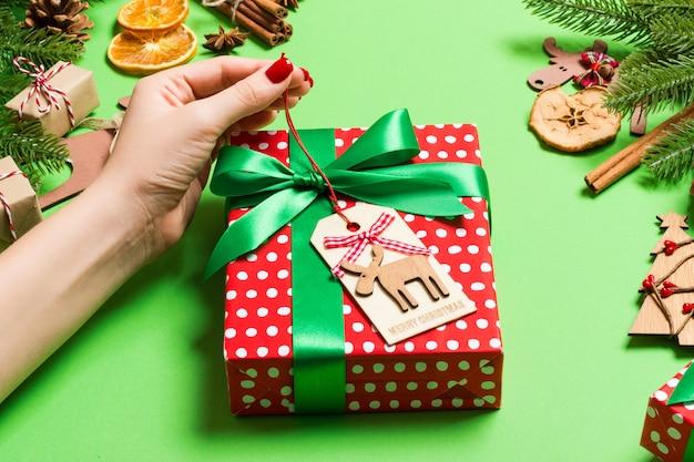 Weibliche hände der draufsicht, die ein weihnachtsgeschenk auf festlichem grün halten. tannenbaum- und feiertagsdekorationen. neujahr