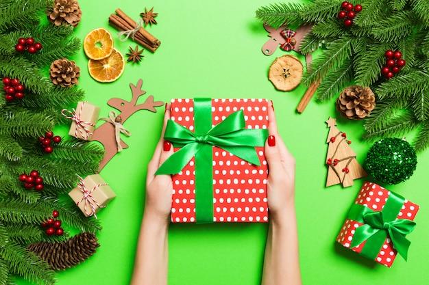 Weibliche hände der draufsicht, die ein weihnachtsgeschenk auf festlichem grün halten. tannenbaum- und feiertagsdekorationen. urlaub