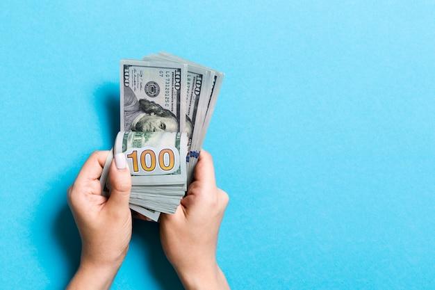 Weibliche hände der draufsicht, die geld zählen. hundert dollarbanknoten auf buntem. geschäft