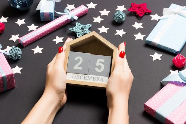 Weibliche hände der draufsicht, die kalender auf schwarzem halten. der fünfundzwanzigste dezember. feiertagsdekorationen. weihnachtszeit