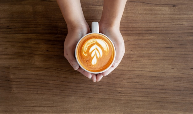 Weibliche hände der nahaufnahme, die tasse kaffees halten