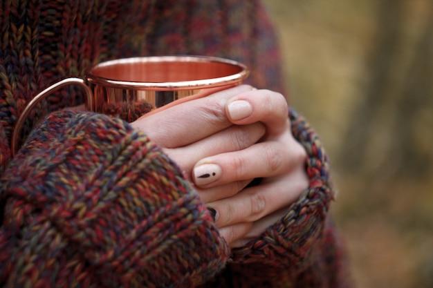 Weibliche hände der nahaufnahme in einer warmen strickjacke, die eine kupferne schale mit tee, gemütliches herbstkonzept hält