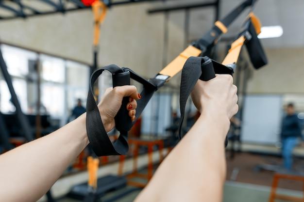 Weibliche hände der nahaufnahme mit eignungsbändern in der turnhalle
