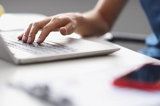 Weibliche hände, die am arbeitsplatz auf der laptoptastatur tippen