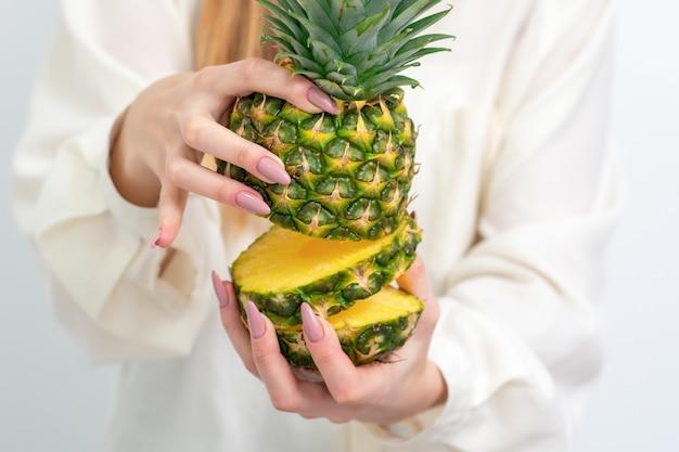 Weibliche hände, die ananas im schnitt halten, schließen oben.