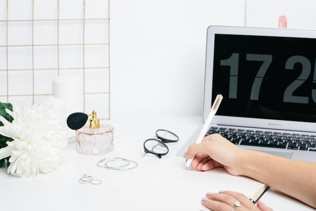 Weibliche hände, die anmerkungen in einem notizblock auf einer weißen tabelle mit einer laptoptastatur machen
