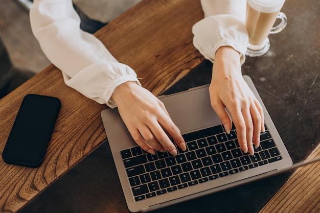 Weibliche hände, die auf computernahaufnahme tippen