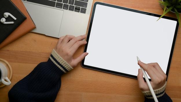 Weibliche hände, die auf digitalem tablett auf hölzernem arbeitstisch mit laptop und zeitplanbüchern zeichnen