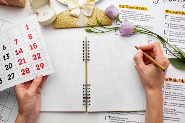 Weibliche hände, die auf ein leeres notizbuch schreiben