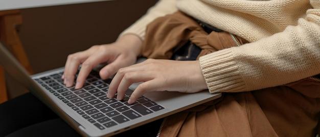 Weibliche hände, die auf laptop auf ihrem schoß tippen, während auf bürostuhl im büroraum sitzen